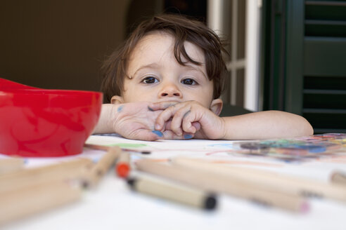 A child leaning on a table littered with colored pencils and art supplies - FSIF00556