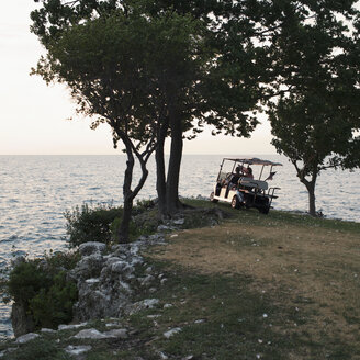 People in a golf cart parked at the edge of the sea - FSIF00571