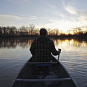 A man in a canoe on a lake at sunset, rear view - FSIF00574