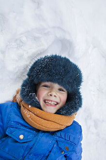 A young cheerful boy wearing warm clothing outdoors lying in the snow - FSIF00607