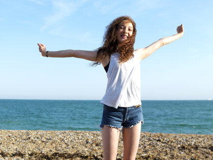 A cheerful teenage girl standing on the beach with her arms raised in exhilaration - FSIF00616