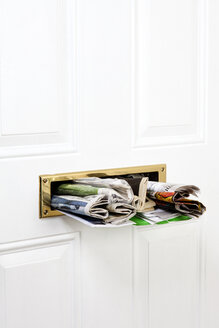 A mail slot stuffed with mail and newspapers, close-up - FSIF00622