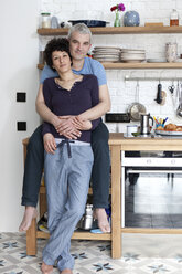An affectionate smiling mixed age couple in their kitchen - FSIF00625