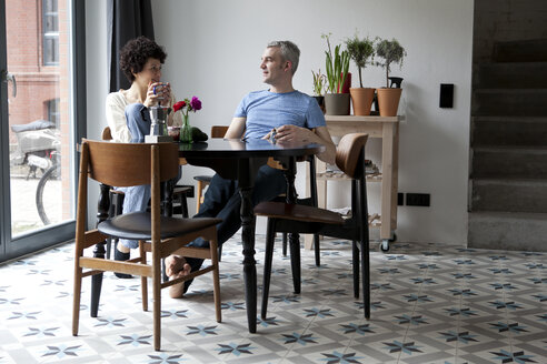 A cheerful hip mixed age couple enjoying breakfast together in their dining room - FSIF00628