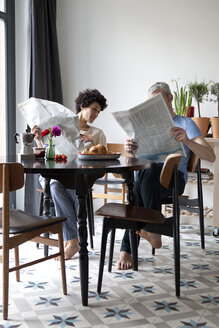 A hip mixed aged couple reading newspapers and having breakfast - FSIF00634