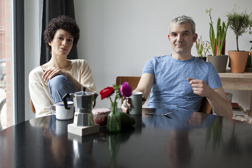 A hip mixed age couple having breakfast in their modern dining table - FSIF00637