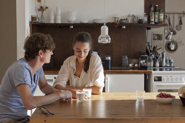 Young couple sitting at dining table - FSIF00706