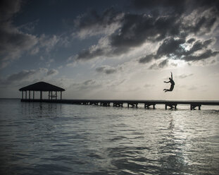 Silhouette person jumping into sea against cloudy sky at dusk - FSIF00826