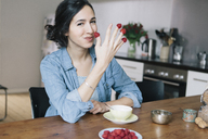Portrait of happy young woman holding raspberries on fingers at home - FSIF00838