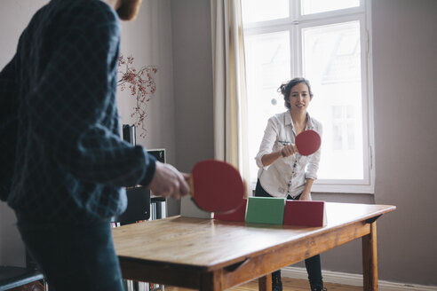 Young woman playing table tennis with man at home - FSIF00862