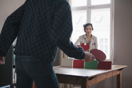 Young woman playing table tennis with man at home - FSIF00877