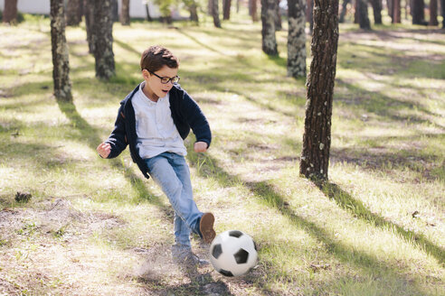 Full length of happy boy playing soccer in forest - FSIF00889