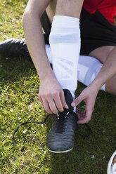 Low section of man tying soccer shoe on field - FSIF00901