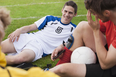 Young soccer players relaxing on field - FSIF00904