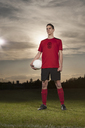 Full length of determined soccer player holding ball on field - FSIF00910