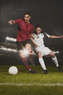 Full length of young male soccer players tackling ball during match - FSIF00919