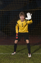Portrait of confident goalie defending soccer net on field - FSIF00928