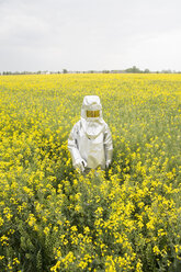 A person in a radiation protective suit standing in an oilseed rape field - FSIF00931