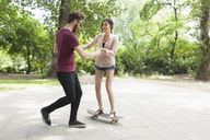 Young man assisting woman in skateboarding on footpath at park - FSIF00964