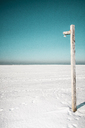 Wooden post on snowy landscape against clear sky - FSIF00985