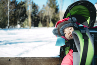 France, Osseja, cute baby girl sleeping in a kid carrier backpack on a bench in a snowy park - GEMF01881