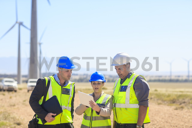 Three engineers with tablet discussing on a wind farm - ZEF14954
