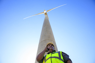 Low angle view of technician on cell phone in front of wind turbine - ZEF14963