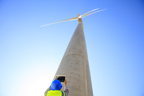 Low angle view of technician taking picture with a tablet of wind turbine - ZEF14966