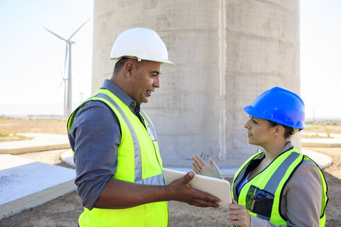 Two engineers with tablet discussing on a wind farm - ZEF14969