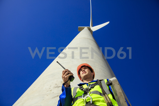Low angle view of technician with walkie-talkie in front of wind turbine - ZEF14972