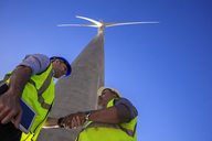 Low angle view of technicians shaking hands in front of wind turbine - ZEF14975