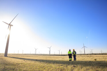 Two engineers discussing on a wind farm - ZEF14978