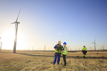 Three engineers with laptop on a wind farm - ZEF14981