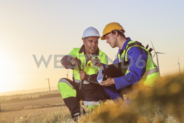 Two technicians discussing on a wind farm at sunset - ZEF14987