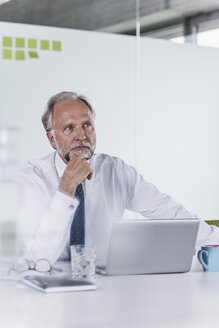 Mature businessman with laptop at desk in office thinking - UUF12725