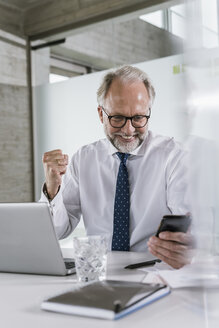 Happy mature businessman at desk in office looking at cell phone - UUF12731