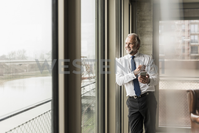 Smiling mature businessman standing at the window looking out - UUF12740