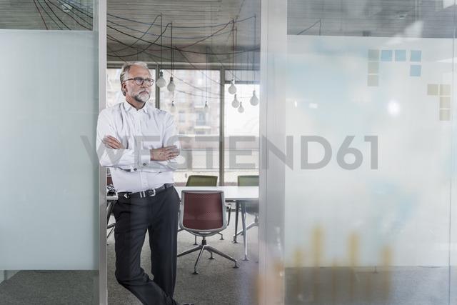 Mature businessman standing in office thinking - UUF12758