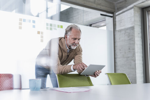 Casual mature businessman using tablet in conference room in office - UUF12764