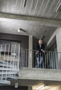 Mature businessman standing in staircase - UUF12782