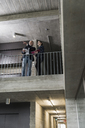 Mature businessman and young woman talking in staircase - UUF12785