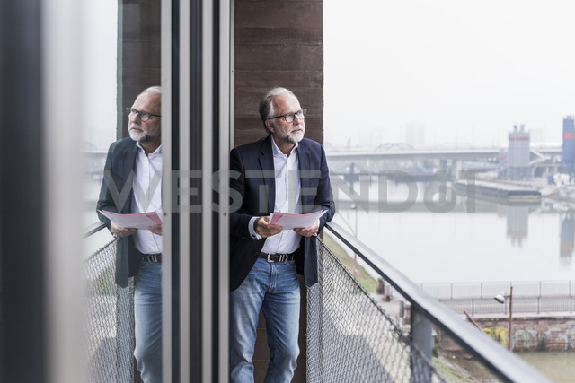 Mature businessman standing on balcony holding papers - UUF12791