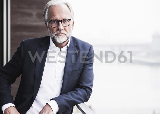 Portrait of mature businessman standing on balcony - UUF12794