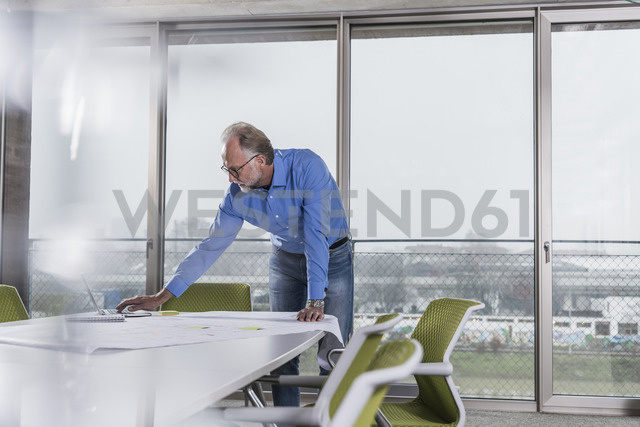 Mature businessman using laptop in conference room in office - UUF12797