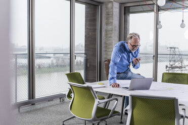Mature businessman using laptop and smartphone in conference room in office - UUF12800