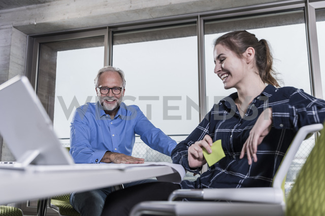 Smiling mature businessman and young woman with tablet in conference room in office - UUF12803