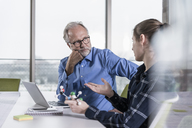 Mature businessman and young woman with atomic model talking in conference room - UUF12806