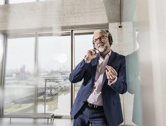 Passionate mature businessman listening to music on headphones - UUF12815