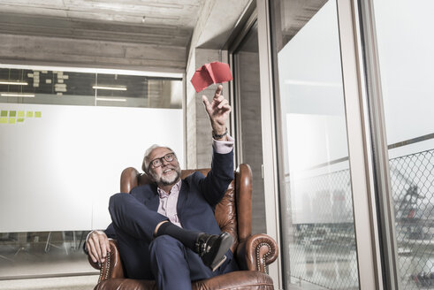 Smiling mature businessman sitting in leather armchair playing with paper plane - UUF12818