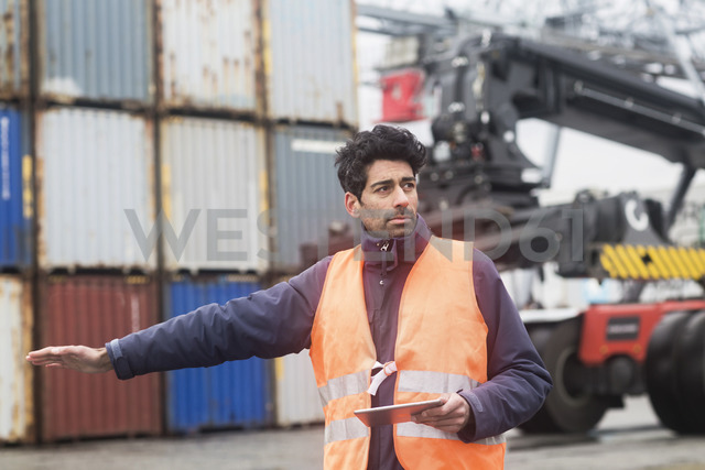 Man with tablet wearing reflective vest at container port - SGF02184
